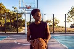 Homme de couleur jouant le basket-ball, boule de rue, homme jouant, compétitions sportives, portrait Afro et extérieur Image stock