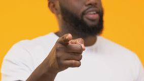 Homme de couleur de sourire dirigeant le doigt dans la caméra d'isolement sur le fond jaune banque de vidéos