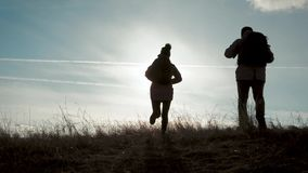 Homme de couples et touriste heureux de femme au sommet de montagne au coucher du soleil dehors pendant une hausse Silhouettes de clips vidéos