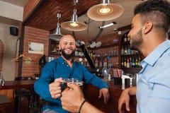 Homme de course de deux mélanges en verres de tintement de barre grillant, tasses potables de prise de bière, se réunir gai d'ami Image stock