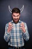 Homme de cri se tenant au-dessus du fond de tableau avec les klaxons tirés Photographie stock
