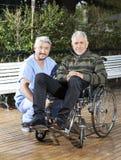 Homme de Crouching By Senior de physiothérapeute dans le fauteuil roulant à la pelouse Image stock