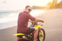 Homme de cycliste avec sa motocyclette de sport sur la plage d'océan Photographie stock libre de droits