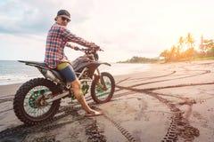 Homme de cycliste avec sa motocyclette de sport sur la plage noire de sable Photo stock