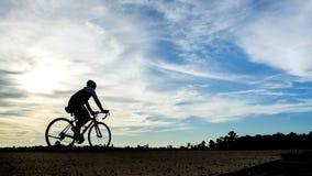 Homme de cycliste de Silouette au coucher du soleil Photographie stock libre de droits