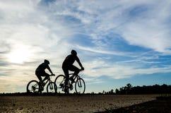 Homme de cycliste de Silouette au coucher du soleil Images stock