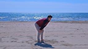 Homme de débutant cessé pour attraper son souffle après avoir pulsé sur la plage de sable de mer clips vidéos