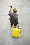 Homme de déplacement marchant avec la valise d'annonce de téléphone portable Image libre de droits