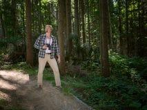 Homme de déplacement marchant dans la forêt d'été Image stock