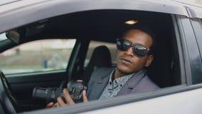 Homme de détective privé s'asseyant à l'intérieur de la voiture et photographiant avec l'appareil-photo de dslr Image stock