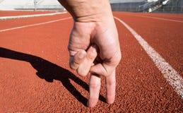 Homme de deux doigts courant sur la voie courante au stade de sport Photos libres de droits