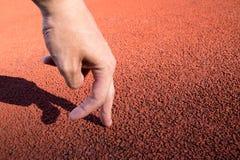 Homme de deux doigts courant sur la voie courante au stade de sport Photographie stock