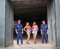 Homme de deux mécaniciens automobiles et deux belles filles sexy Image libre de droits