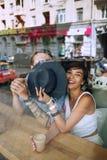 Homme de dissimulation de femme derrière le chapeau en café Photographie stock libre de droits