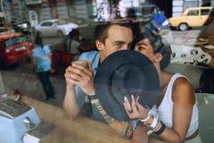 Homme de dissimulation de femme derrière son chapeau en café Photo libre de droits