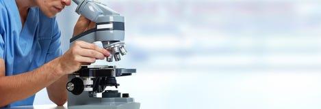 Homme de docteur avec le microscope photos stock
