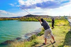 Homme de Fiser jetant sa canne à pêche image stock