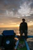 Homme de Fisher, bateau en bois traditionnel et vue d'océan pendant les sunris Images stock