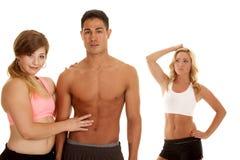 Homme de forme physique avec deux femmes un ABS de contact photos stock