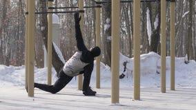 Homme de forme physique faisant l'exercice accroupi sur l'au sol de sports d'hiver extérieur images stock