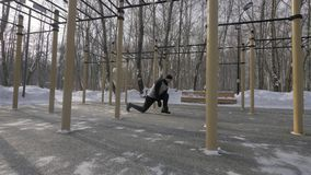 Homme de forme physique faisant l'exercice accroupi sur l'au sol de sports d'hiver extérieur photographie stock