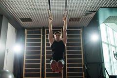 Homme de forme physique faisant l'exercice de plongement utilisant des anneaux dans le gymnase sport Photos libres de droits
