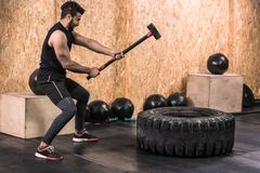 Homme de forme physique de sport frappant le pneu de roue avec la formation de Crossfit de traîneau de marteau, jeune type en bon image libre de droits