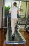Homme de gymnase courant sur le tapis roulant Photo stock