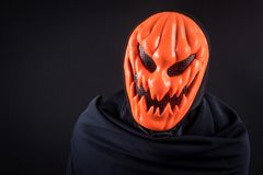 Homme de Halloween avec le masque de potiron sur le fond noir images libres de droits