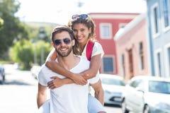 Homme de hanche donnant sur le dos à son girlfriendq Photographie stock