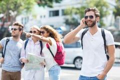 Homme de hanche sur l'appel téléphonique et les amis vérifiant la carte Photo stock