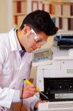 Homme de Hansdome fixant un photocopieur pendant l'entretien utilisant les verres de port d'un travail de tournevis photos libres de droits