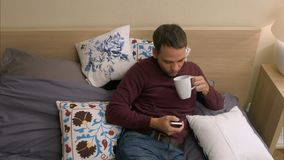 Homme de Hansome à l'aide du téléphone intelligent tout en se trouvant dans le lit la nuit Image stock