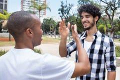 Homme de hippie donnant la haute cinq à l'ami d'afro-américain Image libre de droits