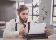 Homme de hippie sur la machine à écrire dans la pièce lumineuse d'espace de travail Photos libres de droits