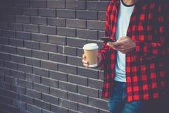 Homme de hippie tenant la tasse intelligente mobile de téléphone et de café envoyant le te image stock