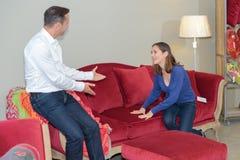 Homme de invitation de femme pour examiner le sofa avec photos stock