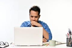 Homme de jeune entreprise couvrant sa bouche de sa main semblant tendue tout en à l'aide d'un ordinateur portable Photographie stock libre de droits