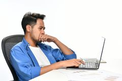 Homme de jeune entreprise couvrant sa bouche de sa main semblant tendue tout en à l'aide d'un ordinateur portable Photo stock
