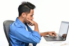Homme de jeune entreprise couvrant sa bouche de sa main semblant tendue tout en à l'aide d'un ordinateur portable Photographie stock