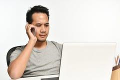 Homme de jeune entreprise parlant au téléphone et à l'aide de l'ordinateur portable Photographie stock