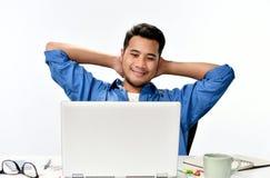 Homme de jeune entreprise s'asseyant dans la posture décontractée faisant ensuite effectuer le travail facilement Images stock