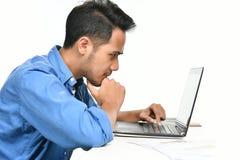 Homme de jeune entreprise s'asseyant dans la posture décontractée tout en travaillant avec l'ordinateur portable Image stock
