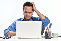 Homme de jeune entreprise semblant soumis à une contrainte tout en travaillant sur un ordinateur portable Images libres de droits