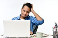 Homme de jeune entreprise semblant soumis à une contrainte tout en travaillant sur un ordinateur portable Image libre de droits