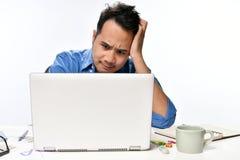 Homme de jeune entreprise semblant soumis à une contrainte tout en travaillant sur un ordinateur portable Photos libres de droits