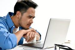 Homme de jeune entreprise semblant tendu tout en à l'aide d'un ordinateur portable Image stock