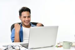 Homme de jeune entreprise soulevant ses mains se sentant heureuses pour réaliser le travail tout en à l'aide de l'ordinateur port Image stock