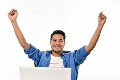 Homme de jeune entreprise soulevant ses mains se sentant heureuses pour réaliser le travail tout en à l'aide de l'ordinateur port Images stock