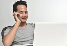 Homme de jeune entreprise souriant tout en parlant au téléphone et ayant l'amusement au travail Images libres de droits